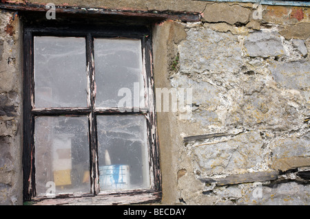 Cobweb covered glass window with peeling paint on the frame against a decrepit stone wall - Stock Photo