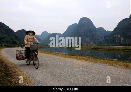 Vietnamese woman on bicycle collecting trash in front of karst mountains, National Park TamCoc, Ninh Binh, North - Stock Photo