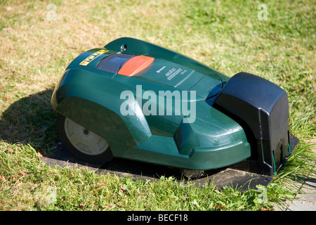 Green automatic robot lawnmower docked in its charging station, top view - Stock Photo