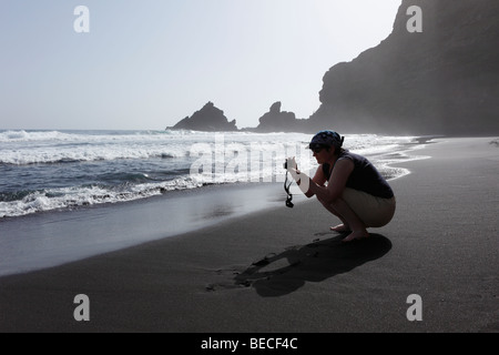 Woman taking pictures of waves, Playa de Nogales, Puntallana, La Palma, Canary Islands, Spain - Stock Photo