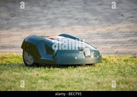 Automatic robot lawn mower cutting grass - Stock Photo