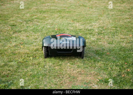 Automatic robot lawn mower cutting grass rear view - Stock Photo