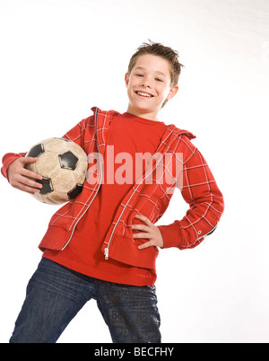 Laughing boy holding a football under his arm - Stock Photo