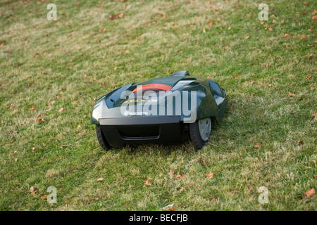 Automatic robot lawn mower cutting grass, rear view - Stock Photo