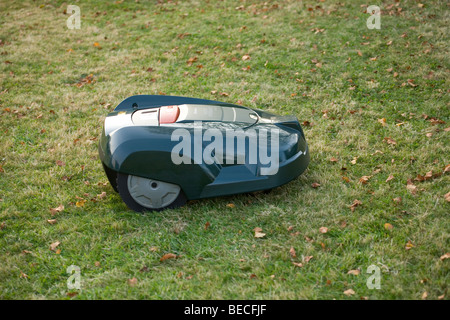 Automatic robot lawn mower cutting grass side view - Stock Photo