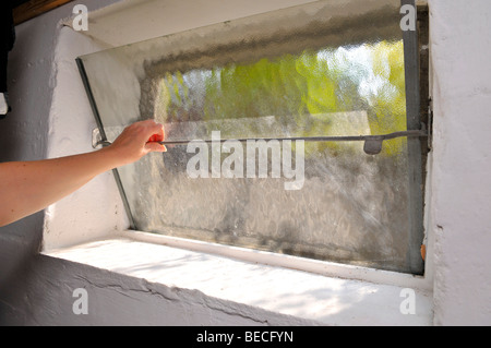 Woman opening a basement window to let some air in - Stock Photo