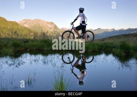 Mountainbiker on the shore of a mountain lake, Northern Tyrol, Austria, Europe - Stock Photo