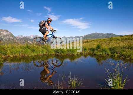 Mountainbiker on the shore of a mountain lake, Northern Tyrol, Austria, Europe - Stock Photo