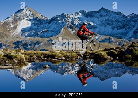 Mountainbiker on the shore of a mountain lake, Kuehtai area, Northern Tyrol, Austria, Europe - Stock Photo