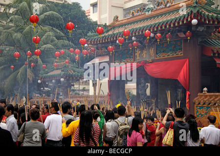 Chinese New Year ceremony with incense sticks in front of the buddhist Kwam Im Tong Hood Che temple in Singapore, - Stock Photo
