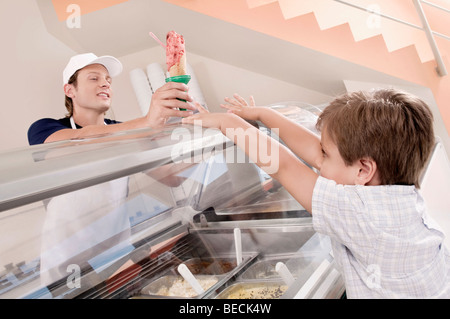 Sales clerk giving ice cream to a boy in an ice cream parlor - Stock Photo