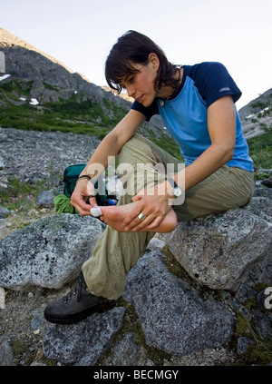 Young woman hiking, backpacking, taping blister on toe, hiker, Klondike Gold Rush National Historical Park, Chilkoot - Stock Photo