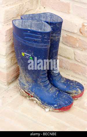 mud caked blue wellington boots neatly paced against a brick wall - Stock Photo