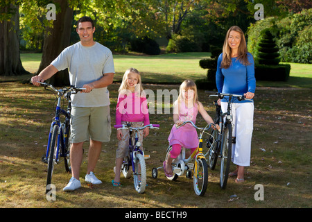 A young family with mother father and two blond daughters riding their bikes in a sun bathed green park - Stock Photo