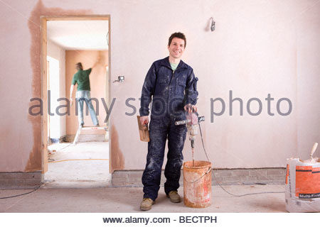 Smiling man mixing plaster in house under construction - Stock Photo