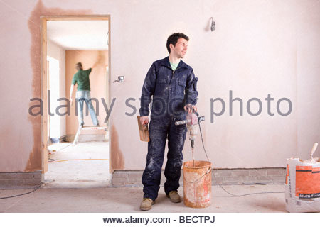 Man mixing plaster in house under construction - Stock Photo
