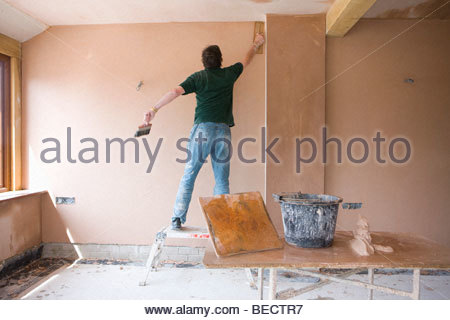 Man on step stool plastering wall in house under construction - Stock Photo