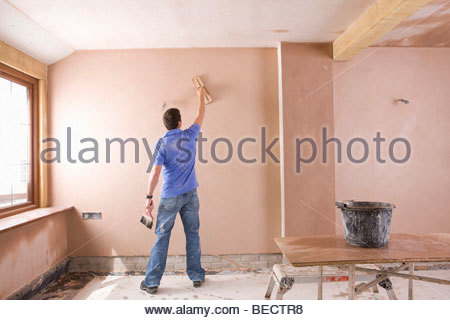 Man plastering wall in house under construction - Stock Photo