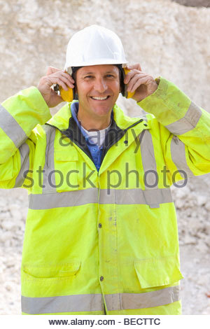 Smiling construction worker wearing ear protectors - Stock Photo