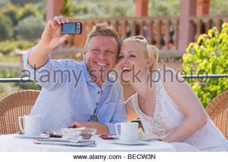 Happy couple taking self-portrait with camera on cafe patio - Stock Photo