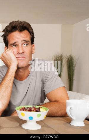 Man frowning at a bowl of fruits - Stock Photo