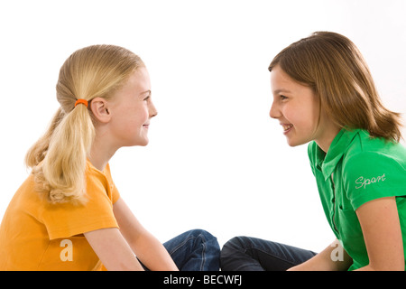 Two girls sitting on the floor, smiling at each other - Stock Photo
