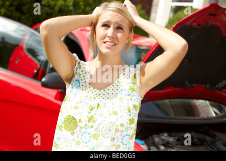 Worried girl with broken down car - Stock Photo