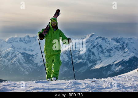 Freestyle skier on the way to a downhill ski run, in front of Karwendel Range, North Tyrol, Austria, Europe - Stock Photo