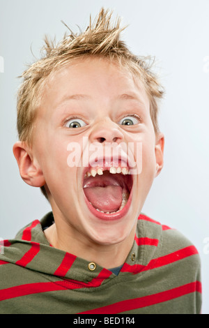 Portrait of a 7-year-old boy with a tooth gap pulling a face - Stock Photo