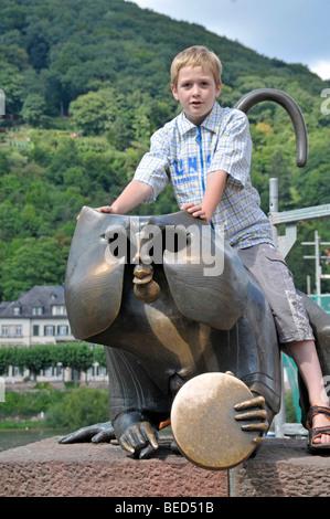 Boy seated on the Bridge Monkey, bronze sculpture of an ape directly beside the Alte Bruecke, Karl Theodor Bridge, - Stock Photo