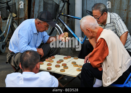 Men playing Chinese Chess in a Hutong street, Beijing CN - Stock Photo