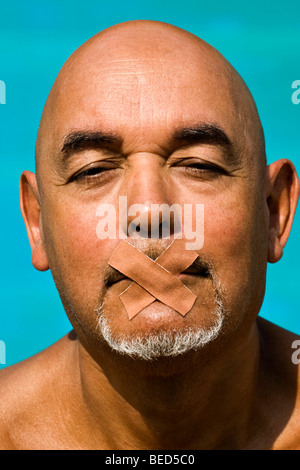Senior citizen with mouth taped over with band-aids - Stock Photo