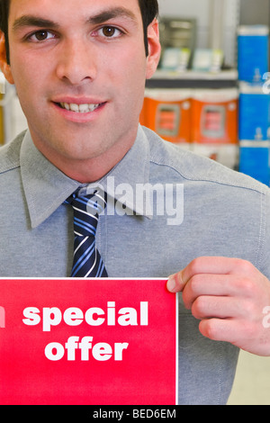 Sales clerk showing a Special Offer sign - Stock Photo