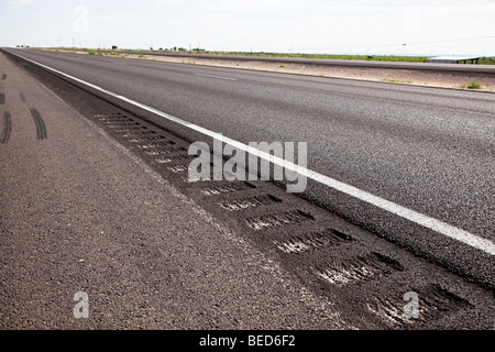 Rumble strip to cause vibration in wheels if vehicle crosses the line at the edge of the road Carlsbad New Mexico - Stock Photo