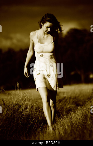 Woman wearing a light summer dress, walking barefooted through a field, imminent thunder clouds in the back - Stock Photo
