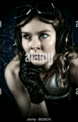 Young woman with headphones, motorcycle goggles and gloves - Stock Photo