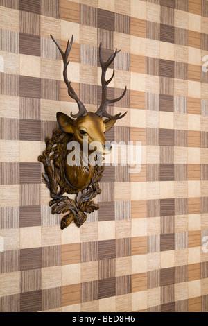 Plastic deer head mounted on imitation wood wallpaper, side view - Stock Photo