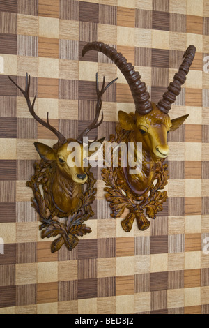 Plastic heads of an ibex and a deer mounted on imitation wood wallpaper, side view - Stock Photo