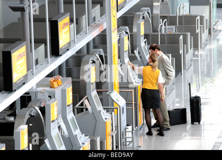 Lufthansa employee explaining to a passenger the Quick-Check-in-Terminal of Lufthansa, Terminal 2 of Munich Airport, - Stock Photo