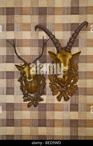 Plastic heads of an ibex and a deer mounted on imitation wood wallpaper, frontal view - Stock Photo