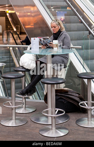 Woman reading a magazine in the departure hall at Duesseldorf Airport, Duesseldorf, North Rhine-Westphalia, Germany, - Stock Photo