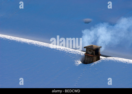 Smoking chimney on a snow-covered roof, Graubuenden, Switzerland, Europe - Stock Photo