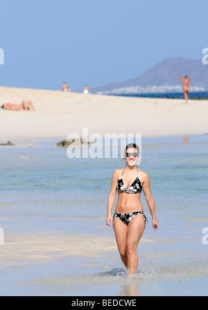 Girl walking on the Playa de la Corralejo Beach, Fuerteventura, Canary Islands, Spain, Europe - Stock Photo