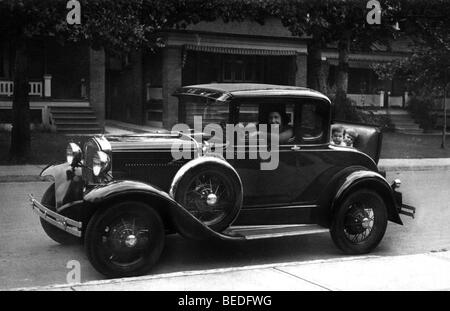 Historic photograph, woman behind the steering wheel, children in the trunk, around 1920 - Stock Photo