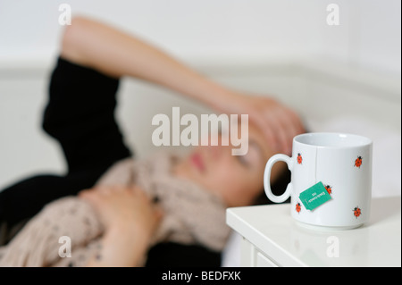 Young woman lying in bed with a cough, cold, flu, ill - Stock Photo
