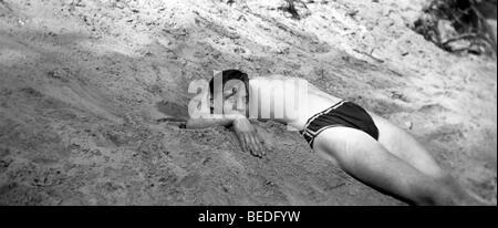 Historic photograph, headless, man buried in sand, around 1920 - Stock Photo
