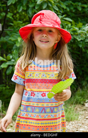 Young girl wearing a red sun hat - Stock Photo