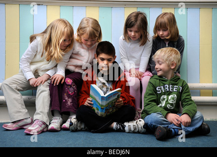 A GROUP OF FOUR GIRLS AND TWO BOYS READING A BIBLE TOGETHER AT A SUNDAY SCHOOL UK - Stock Photo