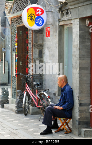 Old man sitting in front of a house entrance at Qiwachang Hutong, Beijing CN - Stock Photo