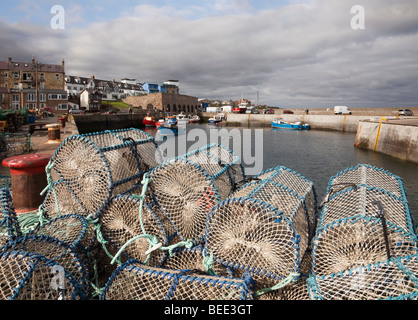 Lobster pots on the harbour wall in fishing village on the north east coast. Seahouses, Northumberland, England, - Stock Photo